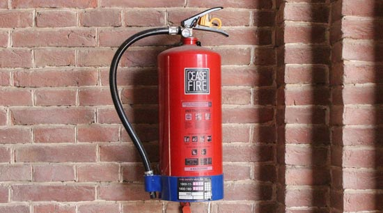 ABC fire extinguisher wall mounted by barbecue grill