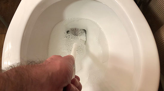 Fix a clogged toilet with a brush