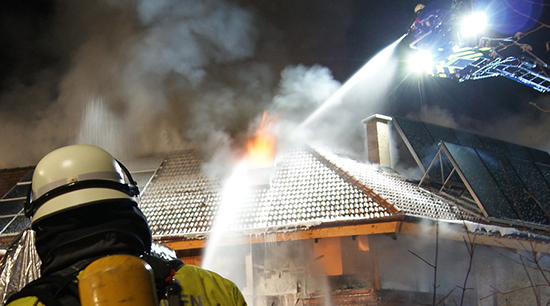 Fire and water damage firemans hoses spray pressurized water everywhere to extinguish flames